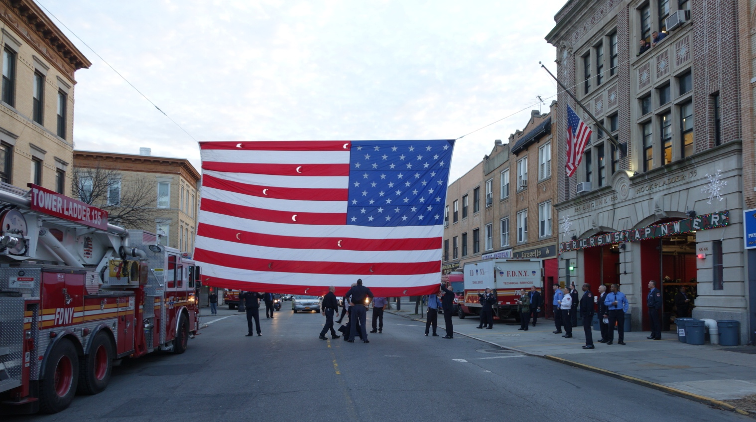 Firefighters from E286/L135 raise a large American flag over the funeral procession route on Myrtle Avenue.
