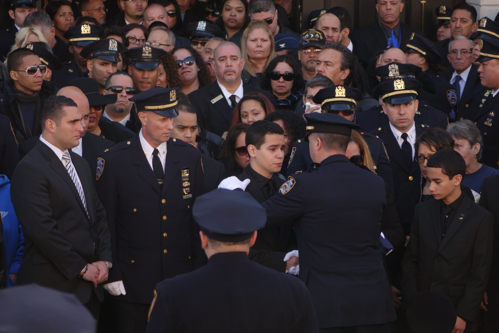 An NYPD officer embraces Det. Ramos' son after presenting the flag from Ramos' casket to his family.