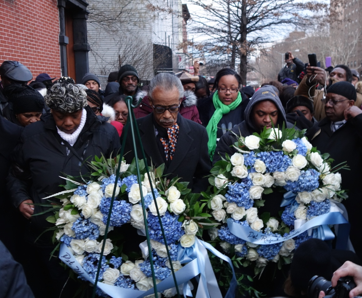 The Rev. Al Sharpton and members of Eric Garner's family pause before placing wreaths at the site where Detectives Rafael Ramos and Wenjian Liu were killed. 1/19/15